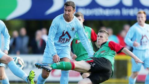 Glentoran's Marcus Kane tries to get a shot in as Mark Scoltock of Institute closes in