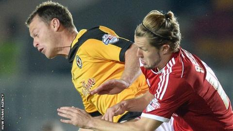 Michael Flynn of Newport County and Jake Reeves of Swindon compete