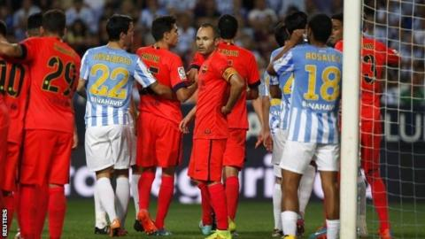 Andres Iniesta looks on as Barcelona and Malaga players argue