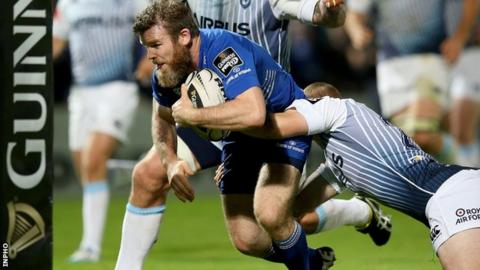 Gordon D'Arcy charges through to score Leinster's third try despite the tackle from Dan Fish