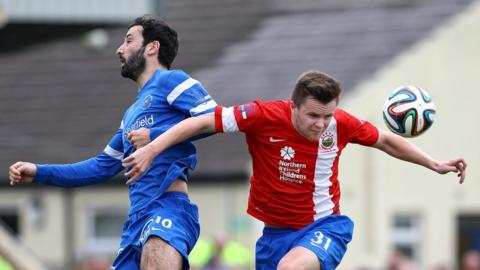 Johnny Lafferty of Ballinamallard and Linfield's Niall Quinn in action at Ferney Park