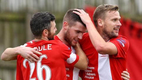Ivan Sproule and Peter Thompson congratulate goal-scorer Stephen Lowry as Linfield win 3-1 at Ballinamallard