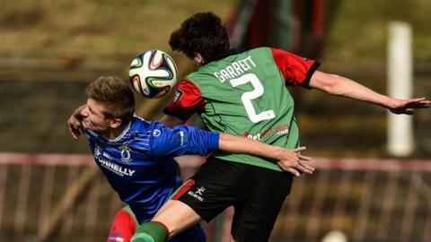 Andrew Mitchell and Willie Garrett in aerial action during Glentoran's game with Dungannon