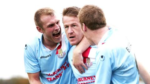 Johnny Taylor and Darren Boyce congratulate Allan Jenkins after his last-minute equaliser for Ballymena against Cliftonville