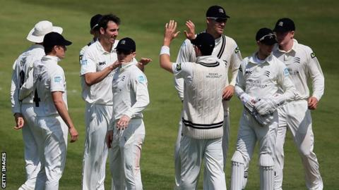 Middlesex bowler Tony Roland-Jones is congratulated by his teammates