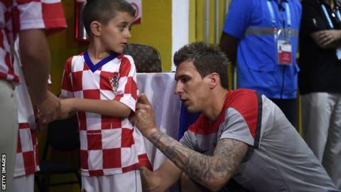 Mario Mandzukic signs a young fan's shirt