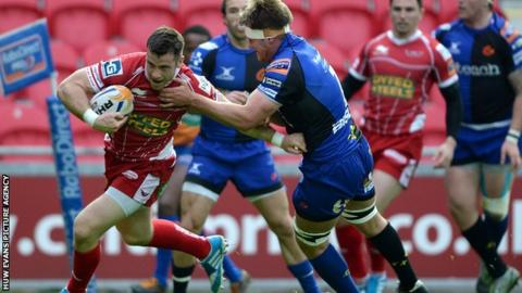 Scarlets' Gareth Davies is tackled by Nic Cudd of the Dragons