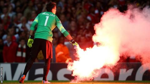 Flares are thrown on to the pitch at Arsenal
