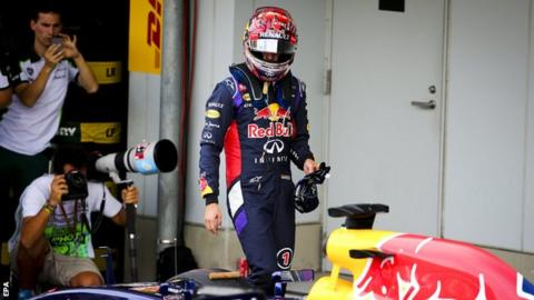 German Formula One driver Sebastian Vettel of Red Bull Racing looks at his car at the end of qualifying at the Suzuka Circuit in Suzuka