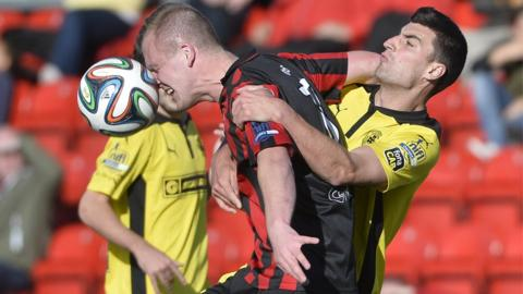 Crusaders striker Jordan Owens gets to the ball ahead of Cliftonville's Johnny Flynn