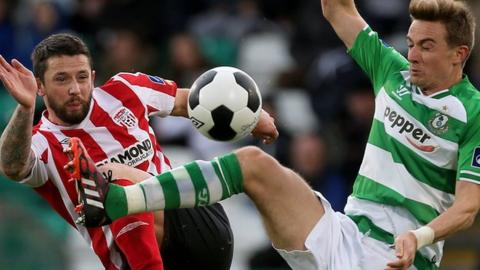 Rory Patterson of Derry goes for the ball with Ronan Finn of Shamrock Rovers