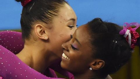 World champion Simone Biles (r) is congratulated by third-placed Kyla Ross