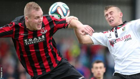 Crusaders striker Jordan Owens and Glentoran's Jay Magee tussle for the ball