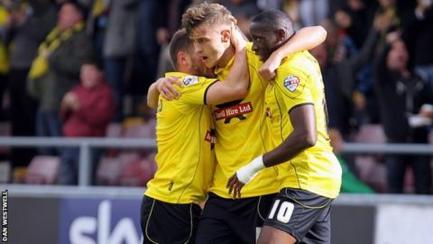 Jacob Blyth (centre) is congratulated after opening the scoring for Burton at Northampton