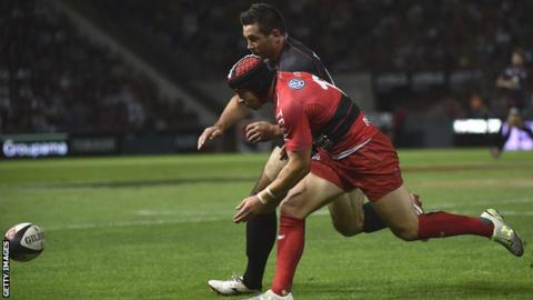 Leigh Halfpenny battles for the ball with Toulouse scrum-half Jean-Marc Doussain during his Toulon debut