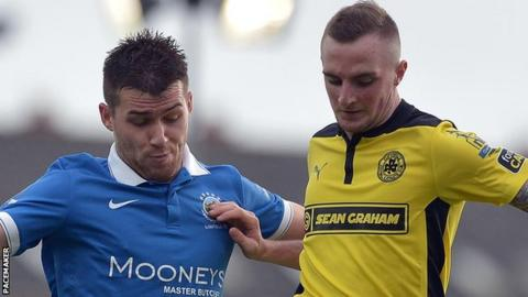 Linfield's Stephen Lowry in action against Jude Winchester of Cliftonville