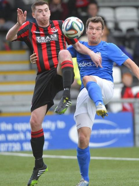 Billy Joe Burns of Crusaders and Glenavon's Kyle Neill compete for the ball during the Irish Premiership match at Seaview
