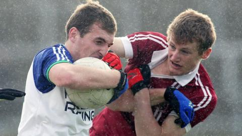 The rain falls at Celtic Park as Ballinderry's Ryan Bell is tackled by Brendan Rogers in Slaughtneil's 1-8 to 0-9 victory in the Derry decider