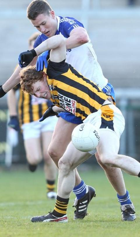Crossmaglen's Garvan Carragher struggles to withstand the challenge of Harps opponent Se Grimley