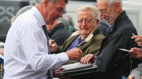 Sam Allardyce signs autographs outside Upton Park