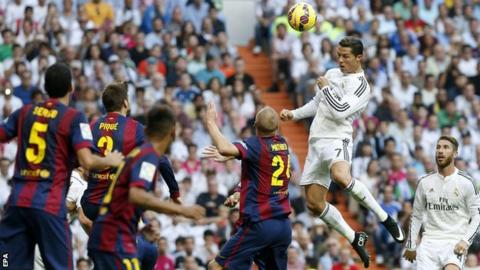 Real Madrid's Cristiano Ronaldo rises above the Barcelona defence