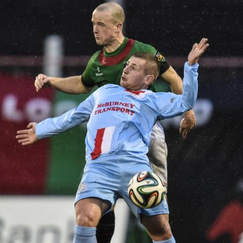 Glentoran defender Barry Holland competes with David Cushley of Ballymena United at the Oval