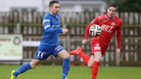 Jason McCartney of Ballinamallard United competes for the ball with Portadown's Peter McMahon