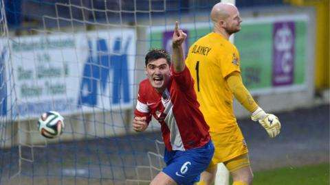 Jimmy Callacher turns away to celebrate after heading Linfield's winner in the 2-1 victory away to Glenavon