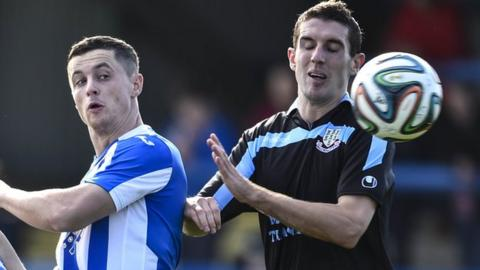 Coleraine's Ruairi Harkin challenges Ballymena United striker Gary Thompson