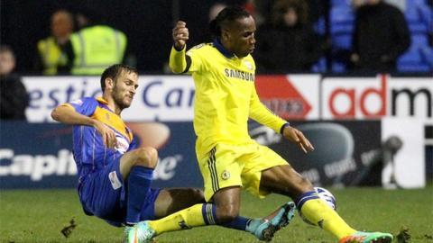 Shrewsbury Town defender Mickey Demetriou tackles Chelsea striker Didier Drogba