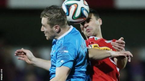 Portadown's Mark McAllister and Johnny Flynn of Cliftonville go up for a high ball