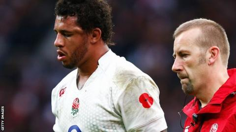 A member of the England medical team escorts Courtney Lawes from the pitch after he sustained a blow to the head in the defeat by New Zealand