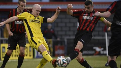 The ball feels the force of this challenge between Cliftonville midfielder Ryan Catney and Crusaders captain Colin Coates at Seaview