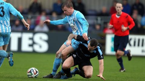 Warrenpoint Town's Liam Bagnall is tackled by Ballymena United opponent Neal Gawley at Milltown
