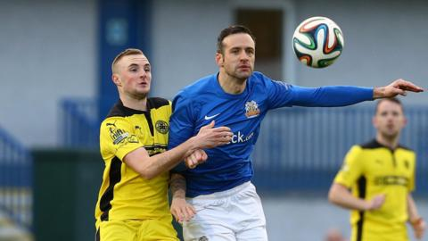 Jude Winchester challenges Ciaran Martyn for possession at Mourneview Park