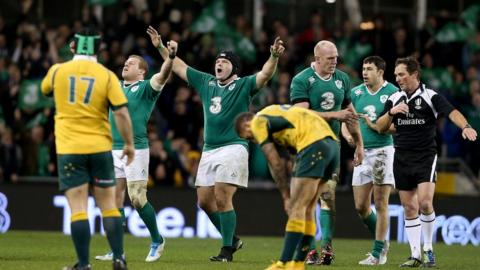 Ireland's players celebrate their 26-23 victory after the final whistle as the Australians look dejected as they fall just short
