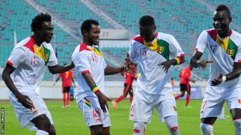 Guinea players celebrate after beating Uganda