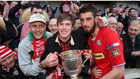 Cliftonville top scorer Joe Gormley celebrates with the Gibson Cup and supporters after the Reds won the Irish Premiership for the second successive season