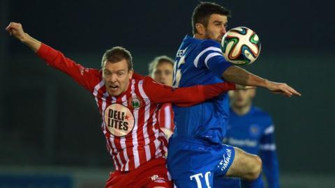 Timmy Grant of Warrenpoint is beaten to the ball by Ballinamallard's Steve Feeney