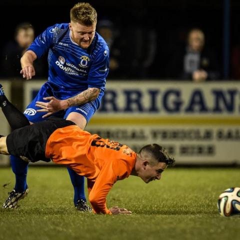 Matt Hazley watches as Glenavon skipper Shane McCabe hits the deck during the game which Dungannon won 2-1