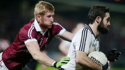 Slaughtneil's Pauldie McGuigan attempts to halt the progress of Omagh player Jason McAnulla during the Ulster club final