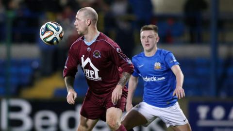 Institute forward Stephen O'Flynn shields the ball from James Singleton in Friday night's game at Mourneview Park