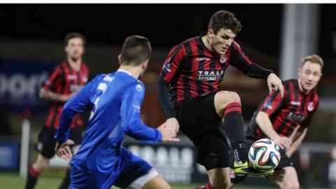 Douglas Wilson of Dungannon Swifts closes in on Crusaders striker Diarmuid O'Carroll at Seaview