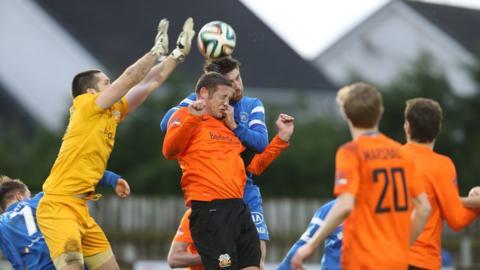 Glenavon goalkeeper James McGrath and defender Kris Lindsay attempt to clear the ball as Mark Stafford applies pressure for Ballinamallard