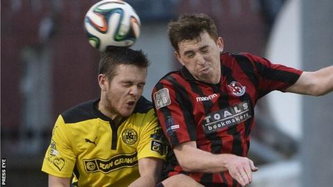 An aerial duel between Cliftonville defender Jaimie McGovern and Crusaders opponent BJ Burns