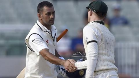 India captain MS Dhoni shakes hands with Australia's Chris Rogers
