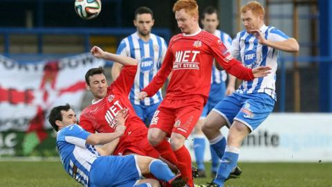 Coleraine's Shane McGinty goes in with a tackle on Portadown pair Michael Gault and Robert Garrett at the Showgrounds