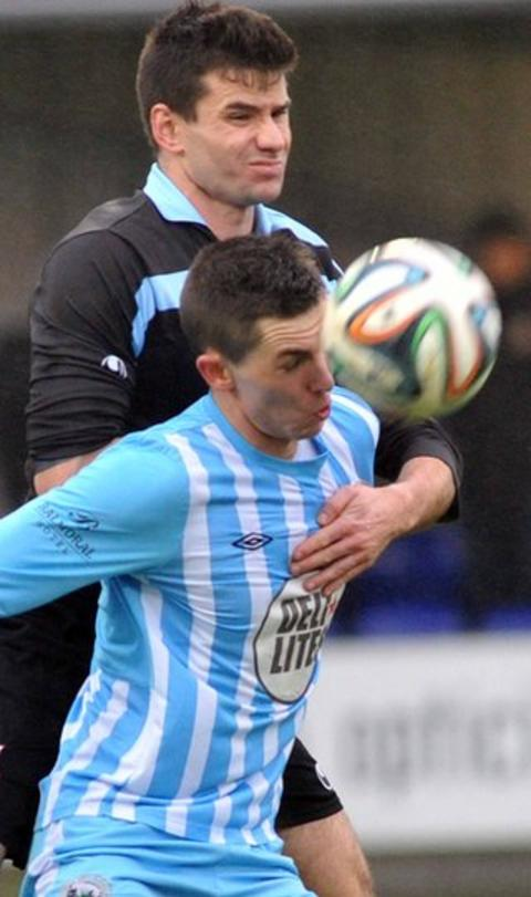 United's Mark McCullagh rises above Daniel Hughes, who netted both goals for Warrenpoint in their 2-0 victory on Thursda