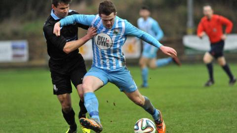 Ballymena United defender Mark McCullagh challenges Warrenpoint Town striker Ciaran O'Connor at Milltown