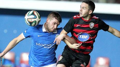 Linfield midfielder Stephen Lowry beats Coleraine's Neil McCafferty to the high ball